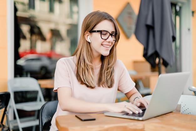Vrouw die op afstand met laptop en telefoon in koffie werkt