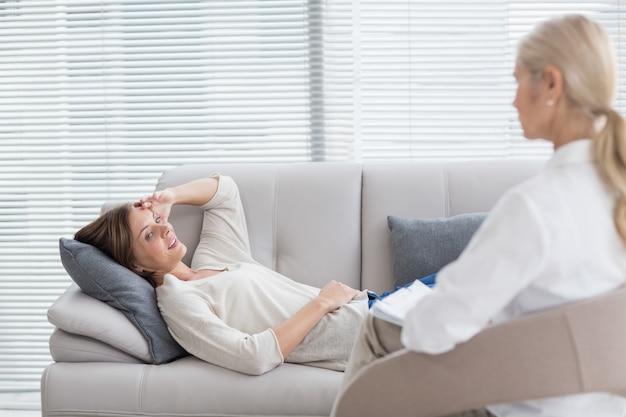 Vrouw die op bank ligt die met therapeut spreekt