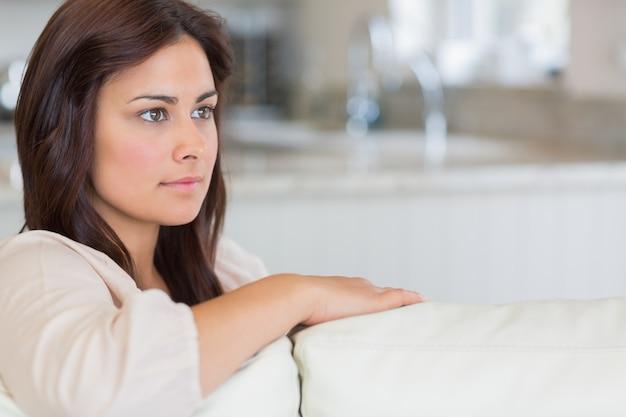 Vrouw die op bank nadenkend kijkt