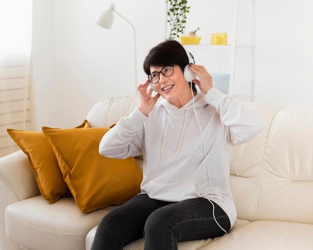 Vrouw die op bank thuis aan muziek luistert