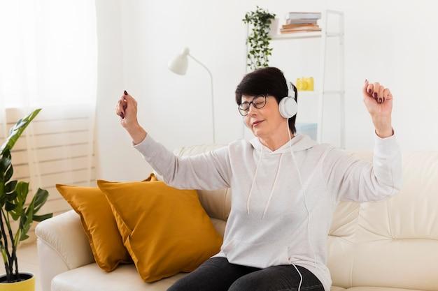 Vrouw die op bank van muziek op hoofdtelefoons geniet