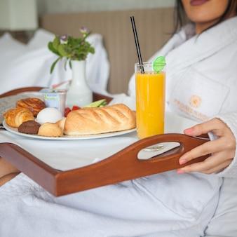 Vrouw die op bed legt geniet van ontbijt op dienblad in hotelruimte