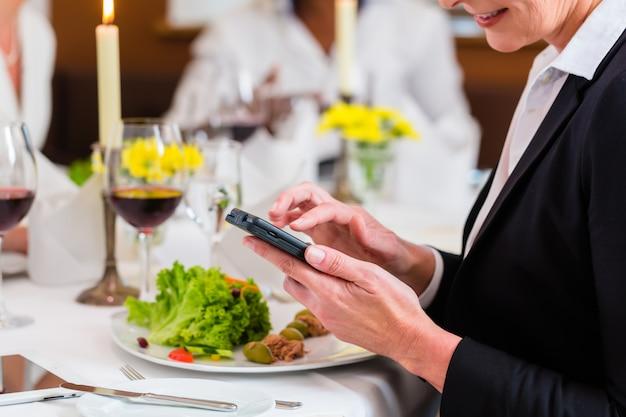 Vrouw die op bedrijfslunch e-mail op telefoon controleert