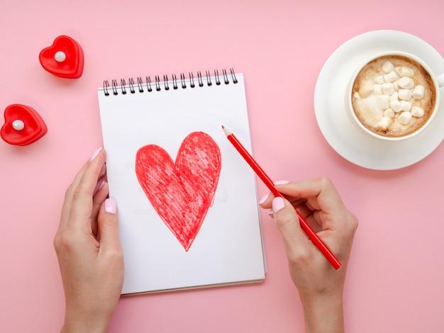 Vrouw die op blocnote met koffie schrijft