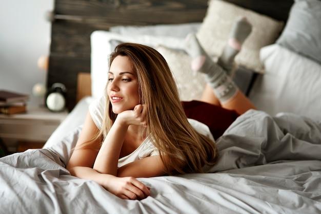 Vrouw die op buik op bed ligt