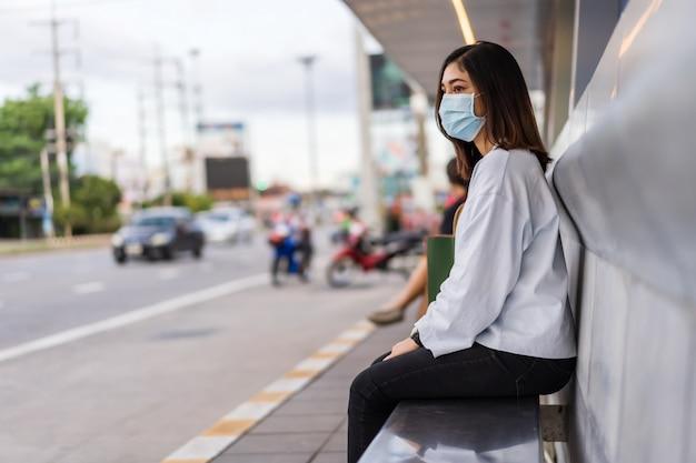 Vrouw die op bus bij bushalte in stadsstraat wacht en gezichtsmasker draagt beschermend voor coronavirus
