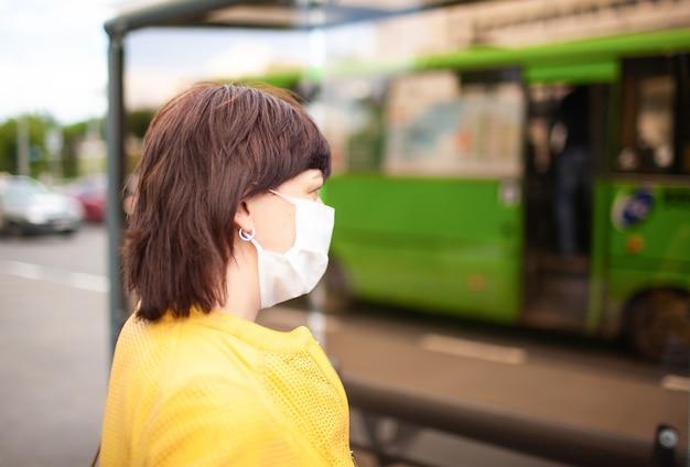 Vrouw die op bus bij bushalte wacht die wit medisch verband draagt