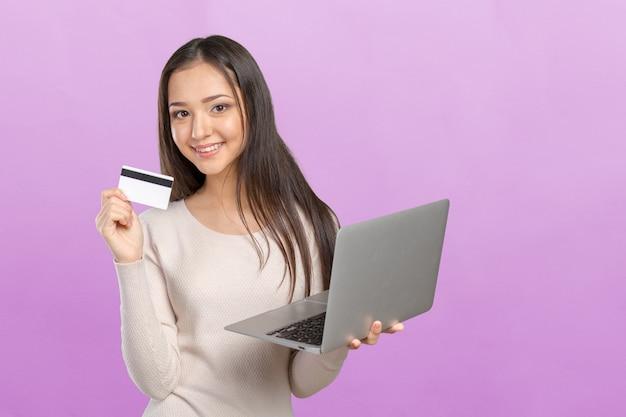 Vrouw die op computer met creditcard winkelt
