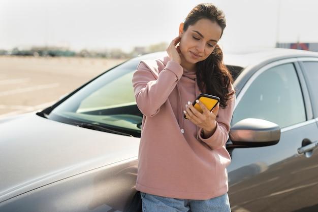 Vrouw die op de auto leunt en haar telefoon bekijkt