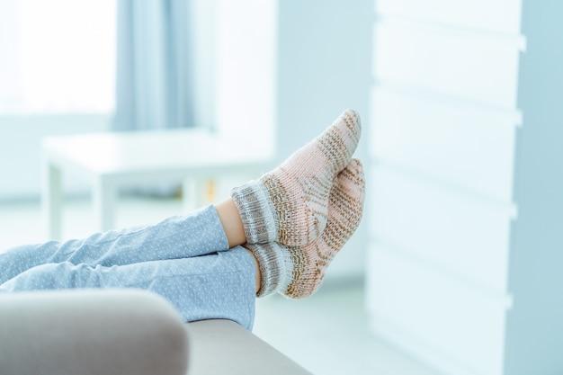 Vrouw die op de bank in pyjama's en comfortabele zachte comfortabele gebreide wintersokken thuis rust