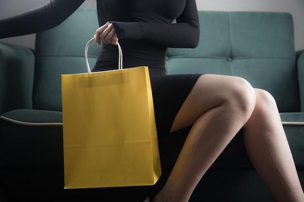 Vrouw die op de bank zit en een cadeauzakje vasthoudt