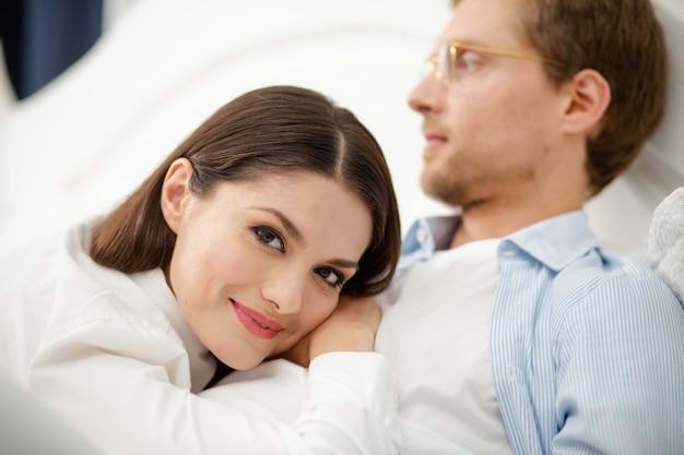 Vrouw die op de borst van haar echtgenoot rust. de kalme zachte vrouw die rust op bemant borst. zoete mooie dame die rust op de borst van haar echtgenoot heeft