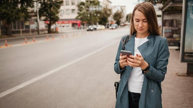 Vrouw die op de bus wacht en haar mobiele telefoon doorzoekt