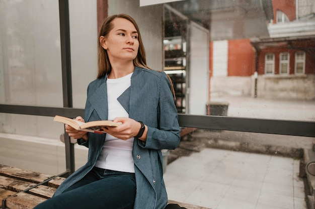Vrouw die op de bus wacht en leest