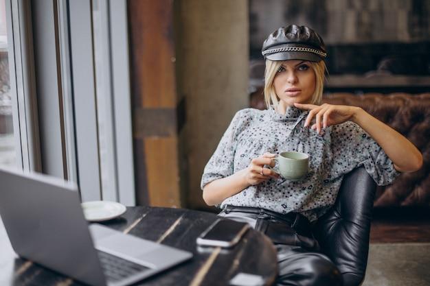Vrouw die op de computer werkt en koffie drinkt