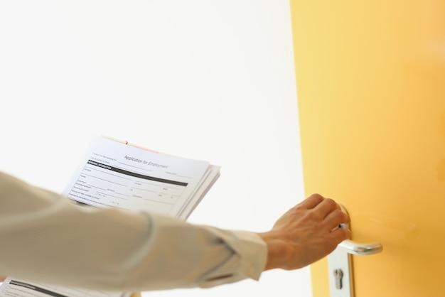 Vrouw die op de deur klopt met een sollicitatieclose-up