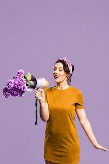 Vrouw die op de megafoon spreekt die door bloemen wordt geblokkeerd