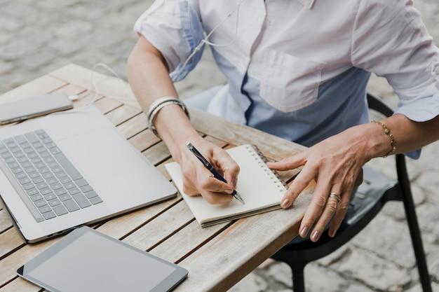 Vrouw die op de mening van de notitieboekje hoge hoek schrijft
