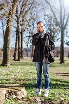 Vrouw die op de mobiele telefoon in het park spreekt