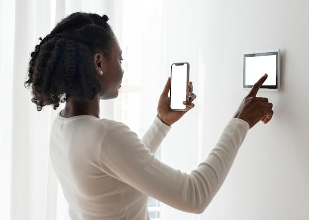Vrouw die op de slimme monitor van het domoticapaneel drukt
