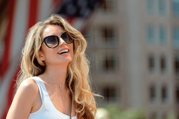 Vrouw die op de straten op de stad van boston dichtbij de centrale haven met amerikaanse vlag glimlacht