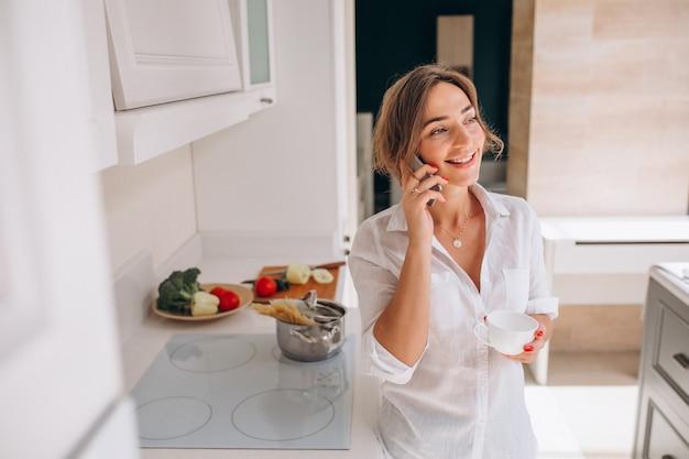 Vrouw die op de telefoon bij keuken en kokend ontbijt spreekt