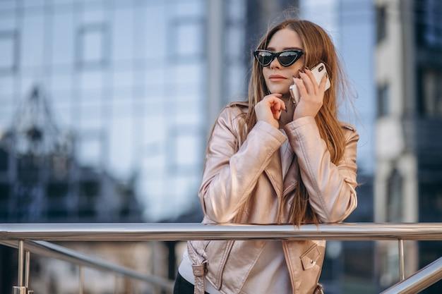 Vrouw die op de telefoon in stad spreekt