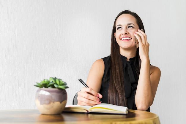 Vrouw die op de telefoon met witte achtergrond spreekt