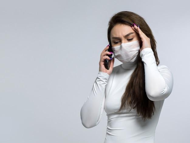 Vrouw die op de telefoon spreekt, aan hoofdpijn lijdt en haar hoofd houdt