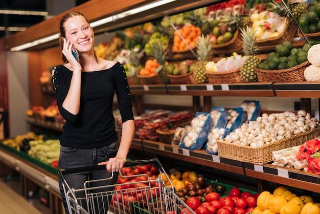 Vrouw die op de telefoon spreekt die de camera bekijkt