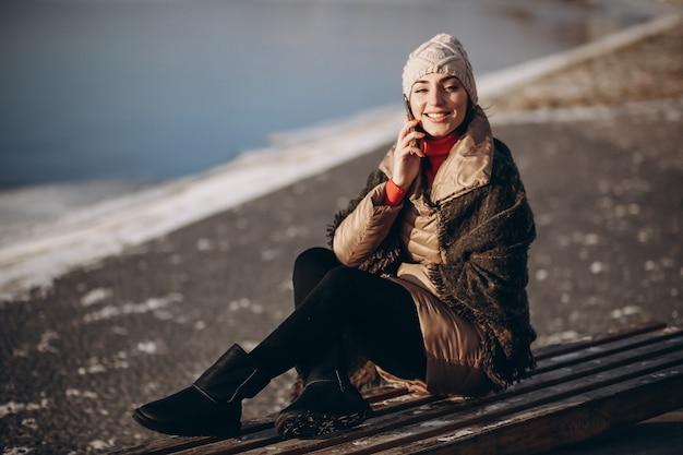 Vrouw die op de telefoon spreekt en op een bank door het meer zit