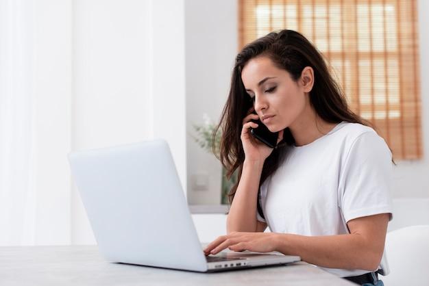 Vrouw die op de telefoon spreekt terwijl het werken aan laptop