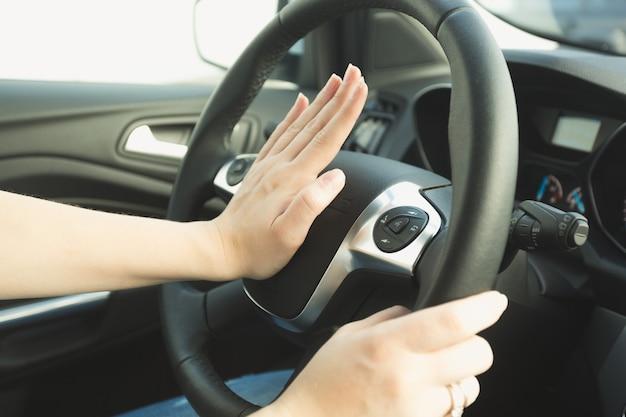 Vrouw die op de toeterknop op het stuur drukt