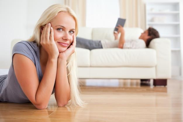 Vrouw die op de vloer ligt terwijl haar echtgenoot een boek leest