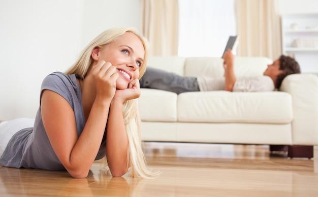 Vrouw die op de vloer ligt terwijl haar vriend een boek leest