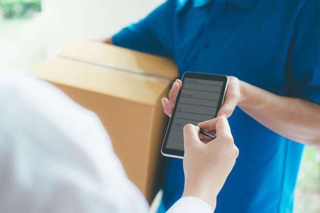 Vrouw die op digitaal apparaat aan leveringspakket ondertekent.