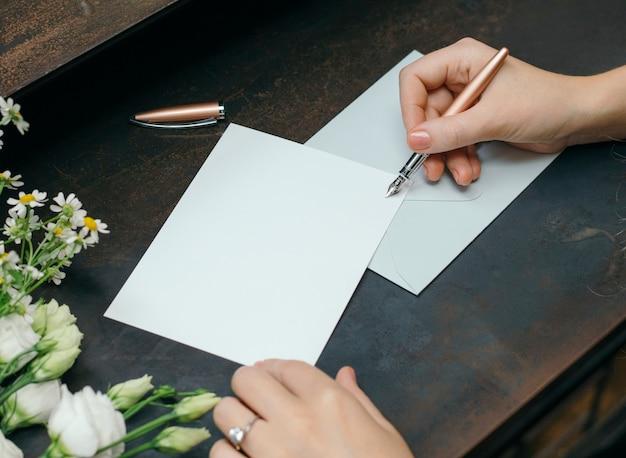 Vrouw die op een blanco kaart schrijft