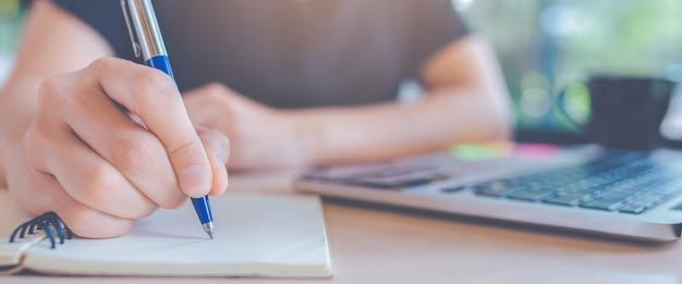 Vrouw die op een blocnote met een pen in bureau schrijft