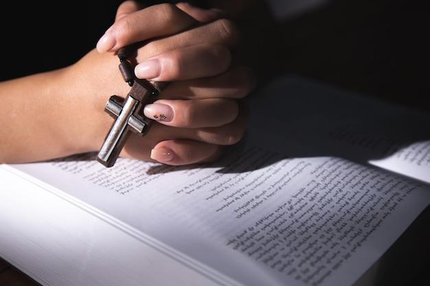 Vrouw die op een boek bidt en een kruis vasthoudt