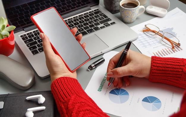Vrouw die op een driemaandelijks rapport schrijft en celtelefoon gebruikt op een grijze bureau dichte omhooggaand. bedrijfsconcept
