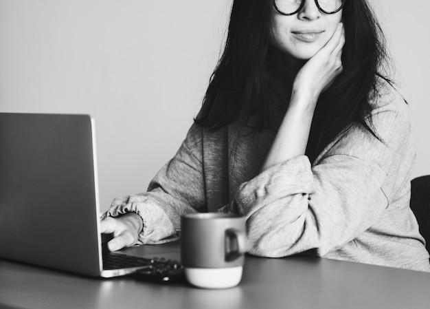 Vrouw die op een laptop in haar huis werkt