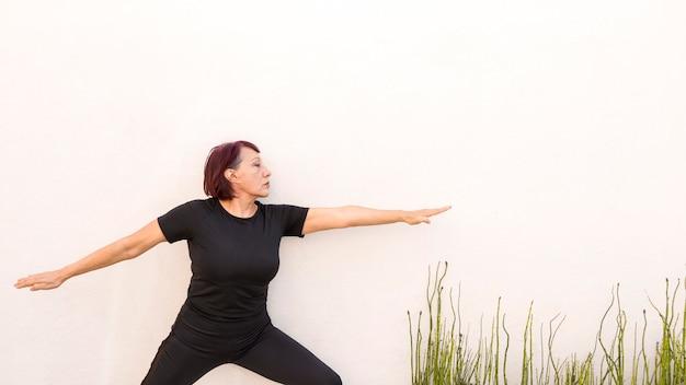 Vrouw die op een muur leunt en oefeningen doet