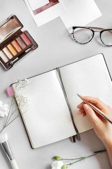 Vrouw die op een notitieboekje schrijft