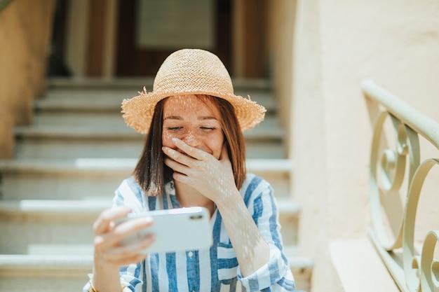 Vrouw die op een online film op haar telefoon letten