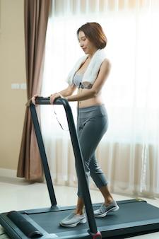 Vrouw die op een tredmolen thuis lopen, gezondheidszorg voor lichaams slank concept.