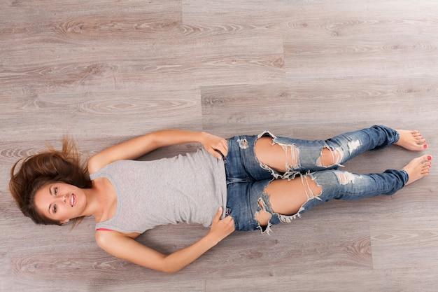 Vrouw die op een vloer met hoofdtelefoons ligt