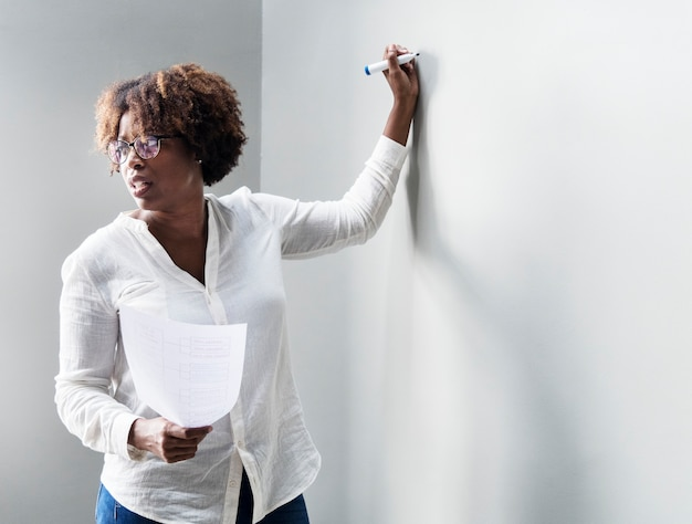 Vrouw die op een witte muur schrijft