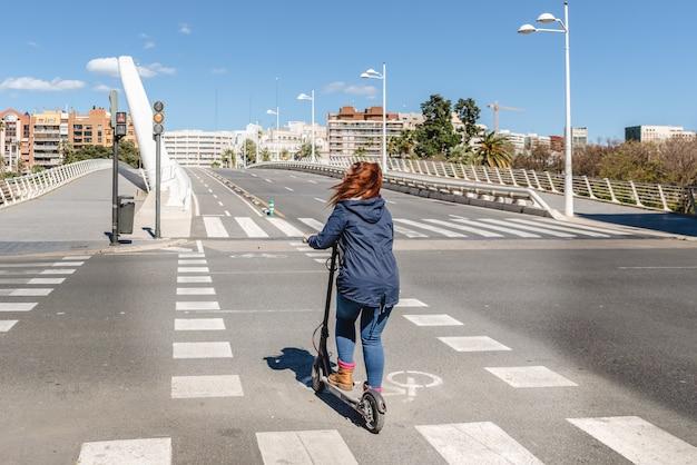 Vrouw die op elektrische autoped een straat zonder auto's op een fietsweg kruist in de stad van valencia.