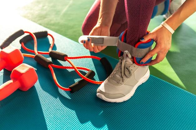 Vrouw die op enkelgewichten zet alvorens zij een training in een gymnastiek, gezondheids en geschiktheidsconcept met domoren op mat begint