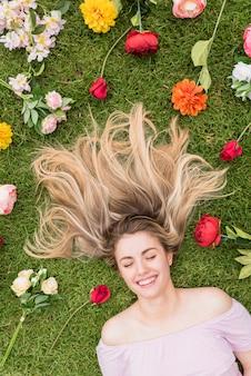 Vrouw die op gras met verschillende bloemen ligt